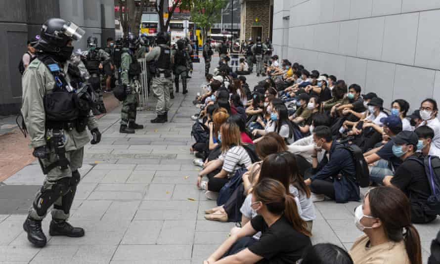 A large group of detainees sit on the ground as police officers set up a cordon in Hong Kong.