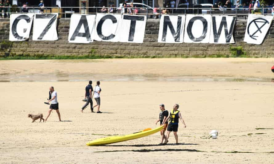 An Extinction Rebellion banner reads 'G7 Act Now' on a beach at St Ives, on Sunday.