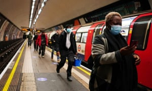A woman wearing a protective face mask on a platform at Clapham Common underground station this morning.