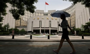Woman walks past the headquarters of the PBOC in Beijing.