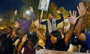 Activists hold their hand up as they protest at the Leimert Park area of Los Angeles, California
