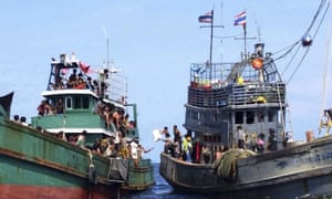 Migrants, believed to be from Burma and Bangladesh, left, receive food, water and other supplies from a Thai fishing boat in the Andaman Sea.