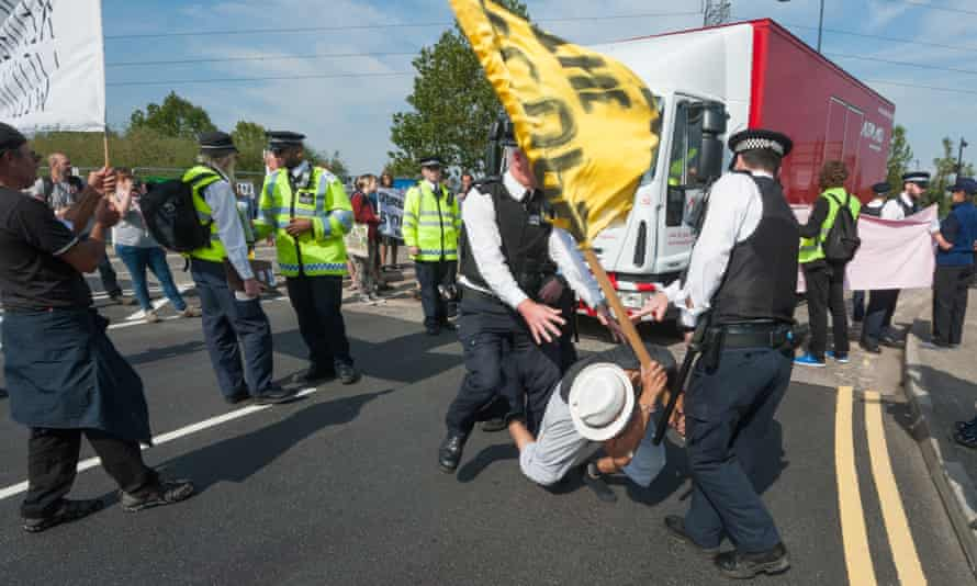 Police move a protester from the road as a truck tries to make a delivery to the DSEI arms fair in London.