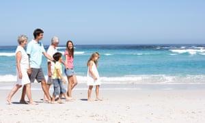 Three generations of a family walking along a sandy beach.