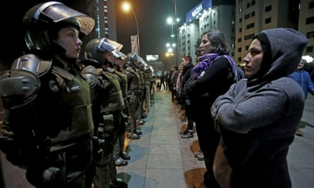 A group of women face a line of policewomen in anti-riot gear before a march protesting sexual harassment in Santiago, Chile, on 1 June.