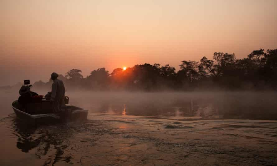 Tourist on boat tour on a misty morning. Kafue River, Kafue National Park, Zambia