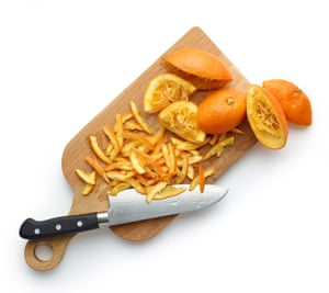 Chopping board with knife and Seville oranges, partly chopped into thin strips of peel