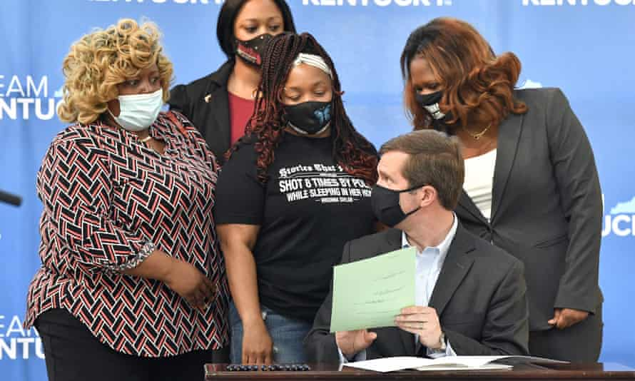 Governor Andy Beshear talks with Tamika Palmer, the mother of Breonna Taylor, back row center, following the signing of a partial ban on no-knock warrants at the Center for African American Heritage in Louisville, Kentucky.