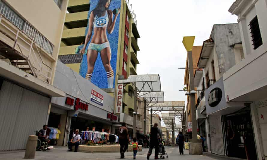 People walk through a shopping area in Río Piedras where many businesses have closed in San Juan, Puerto Rico, on Wednesday.