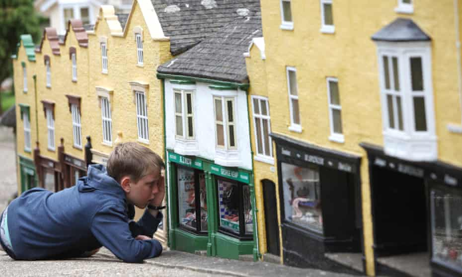 A boy looks like a giant as he looks through a shop window during a visit to The Model Village in Godshill on the Isle of Wight