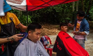 Members of the Thai Military get free hair cuts at the entrance of the cave