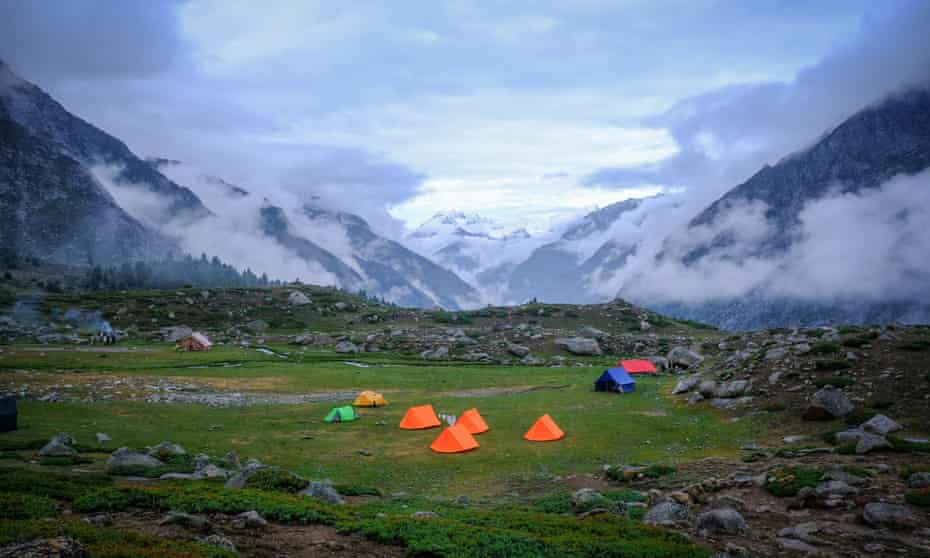 Small tents in a clearing amid cloud covered peaks.