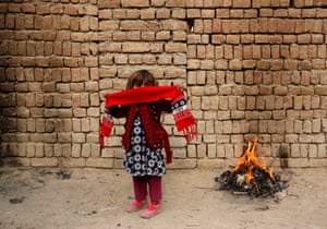 Kabul, Afghanistan. A girl stands next to a fire on a cold winter morning