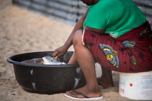 A woman de-scales cassava fish in Robertsport