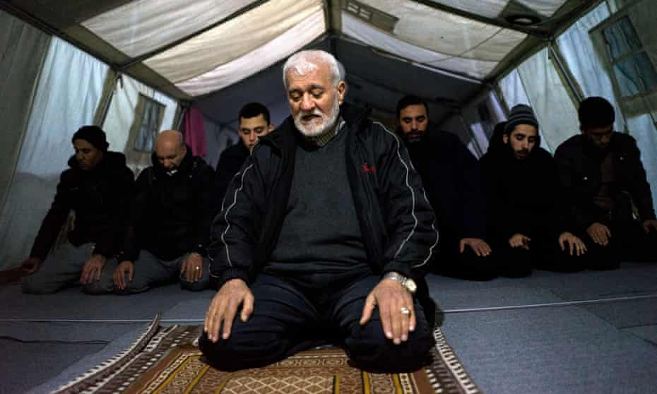 Imam Ali, a 68-year-old Palestinian refugee from Syria, leads prayers in the tented mosque at the Softex refugee camp outside Thessaloniki.