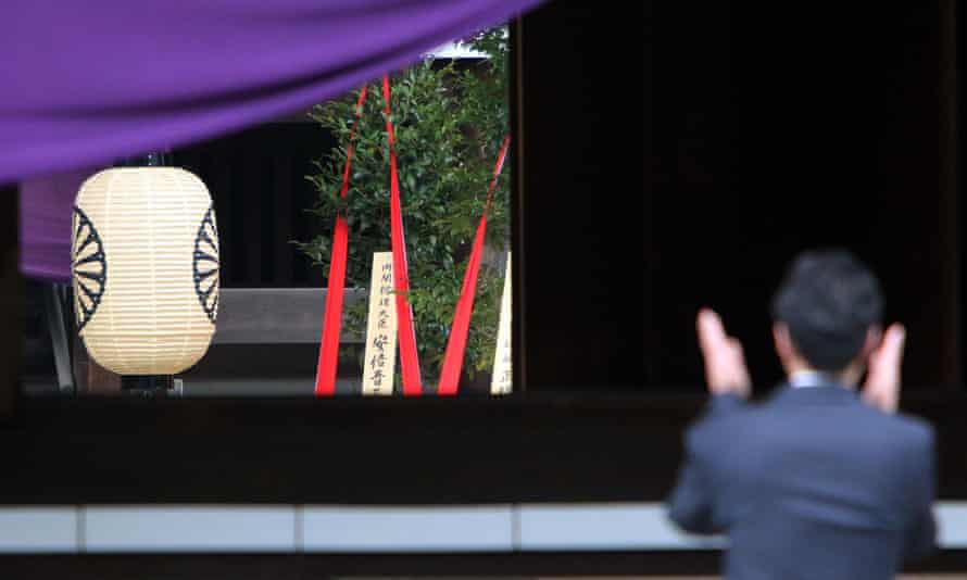 A sacred branch with red ribbons, offered by Shinzo Abe, is seen in the main hall of the Yasukuni war shrine in Tokyo on Tuesday as a man claps hand to offer prayers for people who died during the second world war.