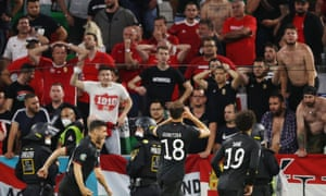 Germany's Leon Goretzka celebrates in front of dejected Hungary fans.