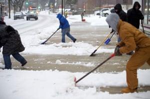 Men shovel a sidewalk in the Roxborough area of Philadelphia, Pennsylvania