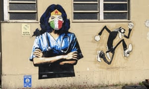 A 'Wonder Woman medic' wearing a face mask with the colors of the Italian flag is painted on a wall in Codogno, the northern Italian town that recorded Italy's first locally spread coronavirus infection early in the pandemic.