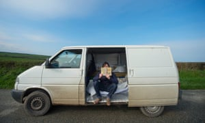 Teacher sitting in his van, which is parked on a road near a field
