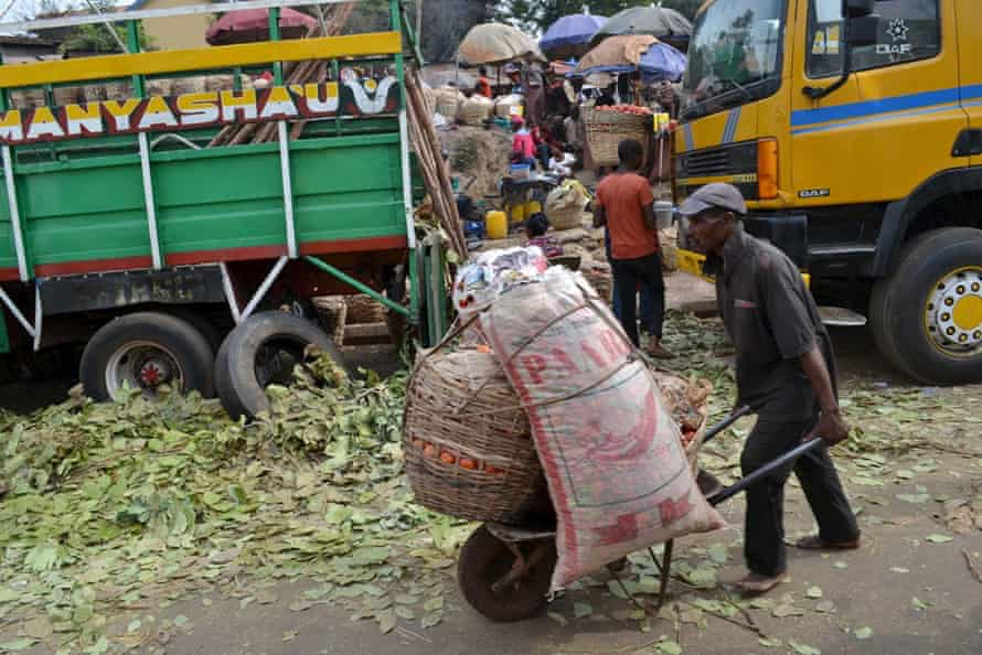 A man pushes a cart filled with baskets of tomatoes at a local market in Enugu.