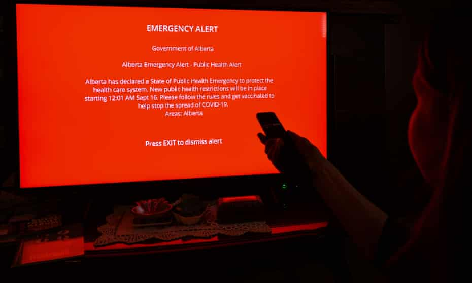A person look at the emergency alert by public health services dispayed on a monitor in Edmonton as new temporary health measures come into effect in Alberta.