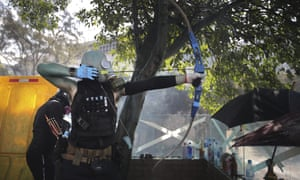A protester prepares to fire a bow and arrow at Polytechic University