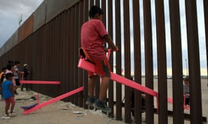 Children in Mexico play on the border fence seesaws.