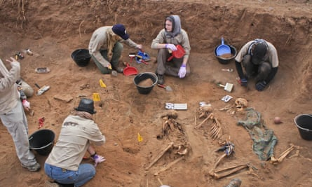In this photo taken 18 February 2014, members of the Peruvian Forensic Anthropology Team work to uncover bodies buried in a mass grave in Hargeisa, Somaliland, a breakaway region of Somalia.