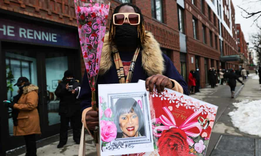 Cornell Sims holds up flowers and a photo of actress Cicely Tyson as he waits for her public viewing at Abyssinian Baptist Church on Monday New York City.