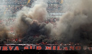 Milan supporters light flares.