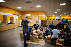 PayPal employees pose for a picture of themselves volunteering to sort produce at Second Harvest Food Bank in San Jose, California.