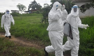 Health workers carry out tests in an area where a 17-year-old boy died from Ebola, on the outskirts of Monrovia, Liberia, on 30 June 2015.