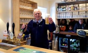 A man holds up a pint behind the bar at the Packhorse Inn