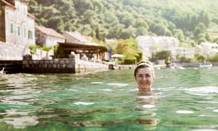 Woman swimming in Kotor Bay on sunny day