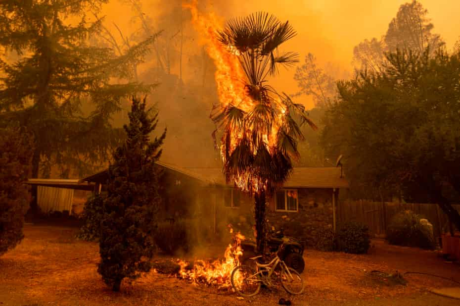 Flames approach a home as a wildfire rages near Lake Berryessa in Napa, California on 18 August.