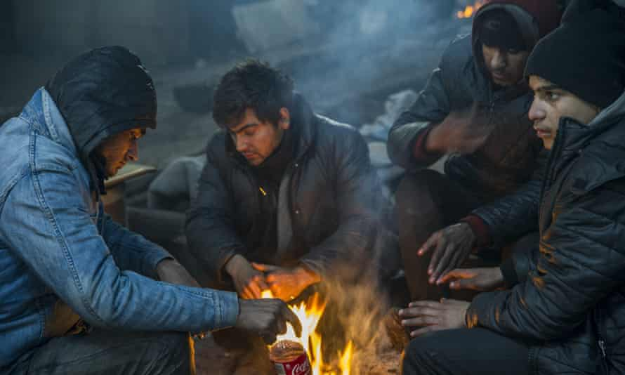Refugees warm themselves by the fire in a derelict warehouse where they live in Belgrade, Serbia.