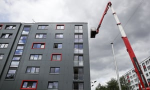 Workers remove cladding for testing from a tower block in Salford.
