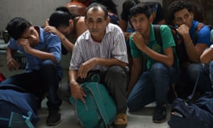 Migrants from Central America crouch in a Mexican detention centre