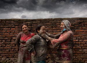 People cover their faces in mud to mark the day