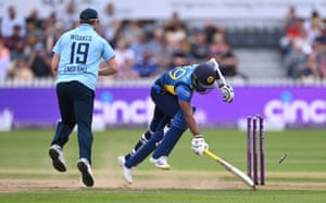 Chamika Karunaratne surves a run out attempt by Chris Woakes.