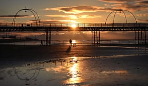 People walk with a dog along the beach at sunset, near Southport Pier