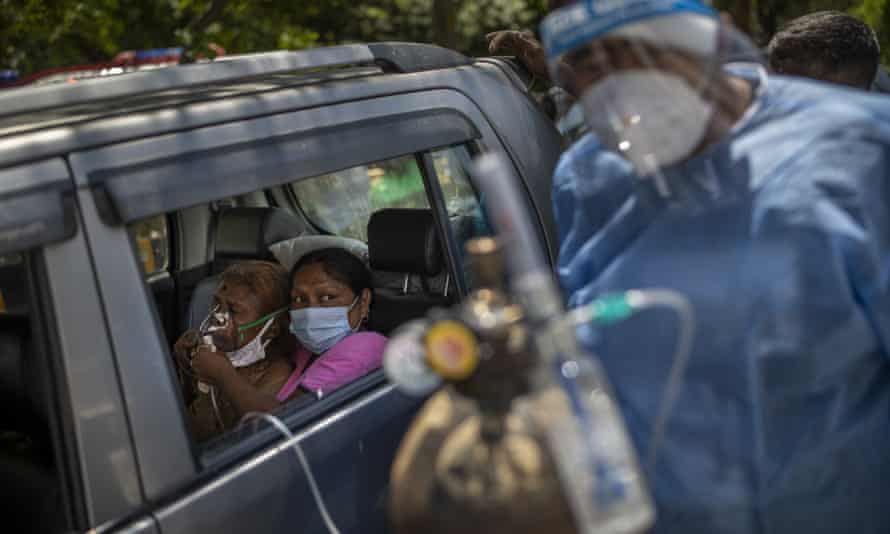 A patient receives oxygen inside a car in New Delhi, where the oxygen shortage has become dire.