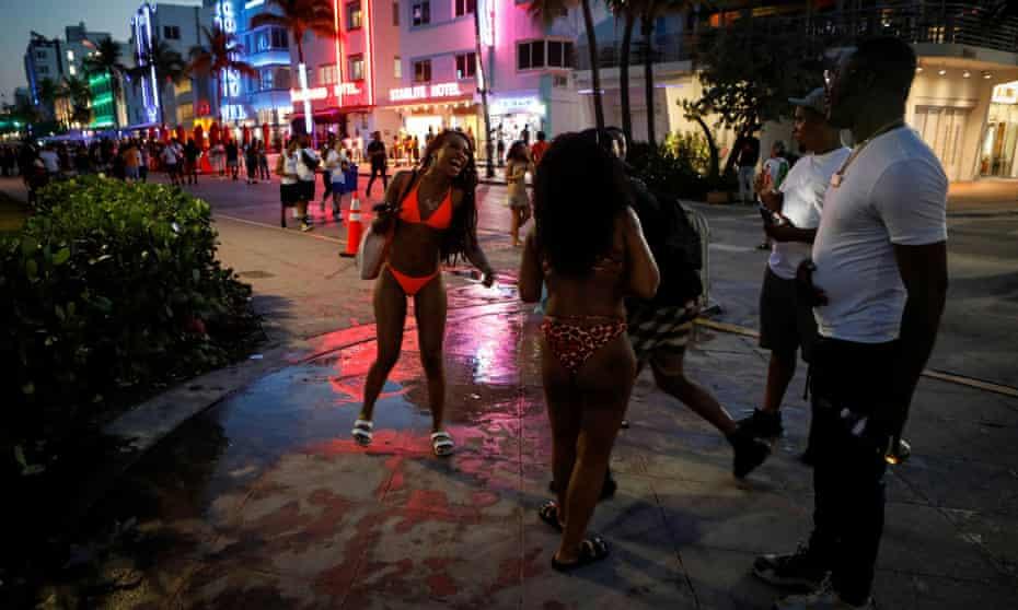 People enjoy spring break festivities ahead of an 8pm curfew imposed by local authorities in Miami Beach this week.