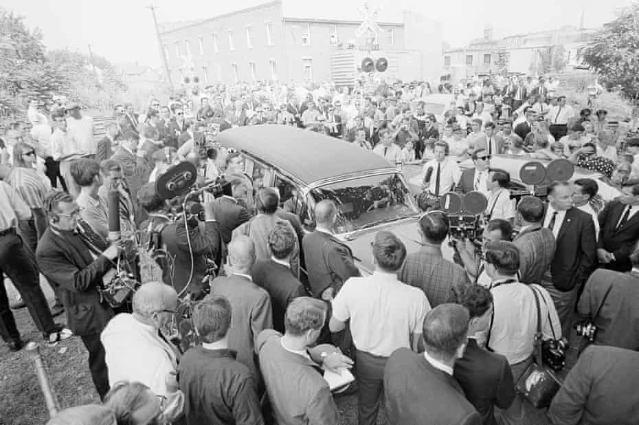 Newsmen and photographers surround a hearse bearing the body of George Lincoln Rockwell.