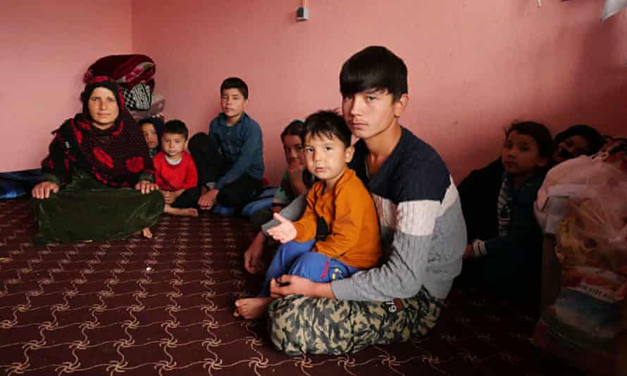 Zebah Gul sits with her eight children in the room at the transit centre in Herat, Afghanistan, after being arrested at the Iran-Turkey border