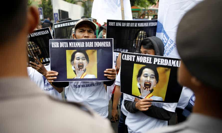 Protesters hold placards critical of Aung San Suu Kyi at a rally in Jakarta this week.