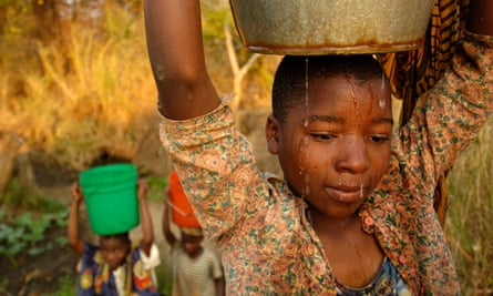 A teenager in Malawi hauls a bucket of water before school