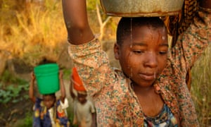 Young women in Malawi carrying water on heads