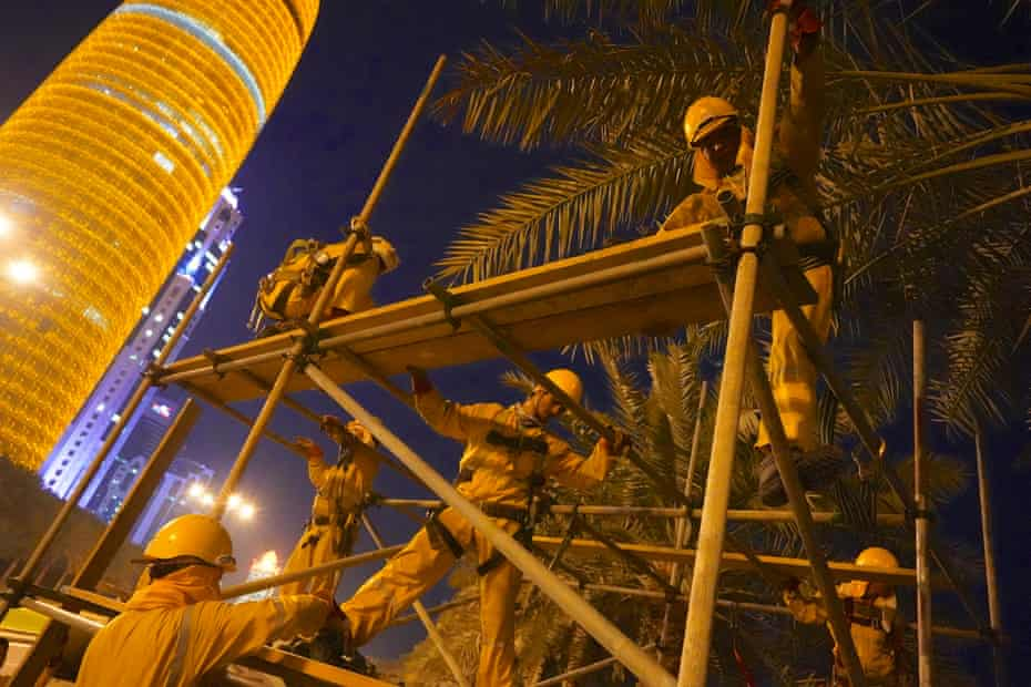 Labourers from Nepal put up scaffolding for the launch of the World Cup logo. They start work long before sunrise to avoid the heat.